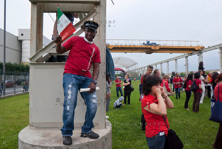 "Sesto San Giovanni (Milano), iniziativa di Radiopopolare per celebrare i 150 anni dell'unità d'Italia: 1000 cittadini italiani di origine straniera indossano una maglietta rossa e sfilando in corteo impersonano i ""nuovi garibaldini"". L'arrivo al Carroponte --- Sesto San Giovanni (Milan), independent Radio station Radiopopolare initiative to celebrate the 150th anniversary of the unification of Italy: 1000 Italian citizens of foreign origin wear a red shirt and march in procession embodying the ""new follower of Garibaldi"". The arrival at the Carroponte"