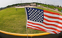 An American flag flies from the outfield of a baseball game.