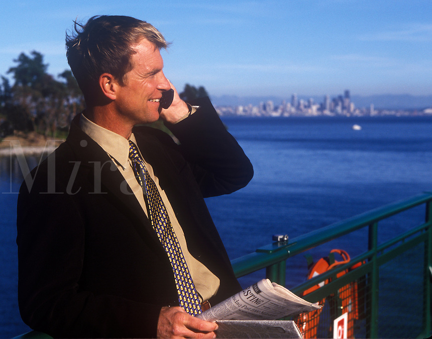 Businessman  talks on cell phone while commuting by ferry.