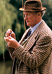 Trout fishing on the River Test Hampshire. Older man in tweed jacket and brown fedora hat fly fishing 1985. 1980s UK.