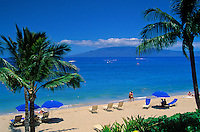Sunbathing on Kaanapali beach, west coast Maui, with view of the island of Lanai
