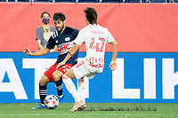 FOXBOROUGH, MA - MAY 22: John Tolkin #47 of New York Red Bulls pressures Carles Gil #22 of New England Revolution during a game between New York Red Bulls and New England Revolution at Gillette Stadium on May 22, 2021 in Foxborough, Massachusetts.