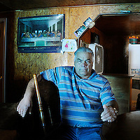 Hilton Chaisson sits in a house with a picture of The Last Supper behind him. Hilton is a fisherman from Isle Jean Charles, a predominantly Native American community on the coast in southeast Louisiana. His family's house has been flooded nearly a dozen times due to increasingly damaging hurricanes. The island is particularly affected by coastal erosion. Residents are seeking higher ground and only 70 residents remain of the 300 residents at the peak of population.