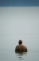 A bald man stands alone in the waters of a lake in St. Mary's, Ohio.