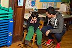 Education Preschool 3-4 year olds high school student volunteering talks to sad boy sitting by himself