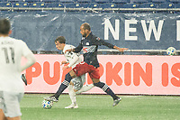 FOXBOROUGH, MA - NOVEMBER 1: Teal Bunbury #10 of New England Revolution comes in to tackle Griffin Yow #22 of DC United during a game between D.C. United and New England Revolution at Gillette Stadium on November 1, 2020 in Foxborough, Massachusetts.