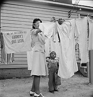 A woman hanging out washing with her young son in front of the community building in a FSA (Farm Security Administration) housing relief camp for African Americans. Arlington, Virginia, 1942.<br /> <br /> Photo by Marjory Collins.