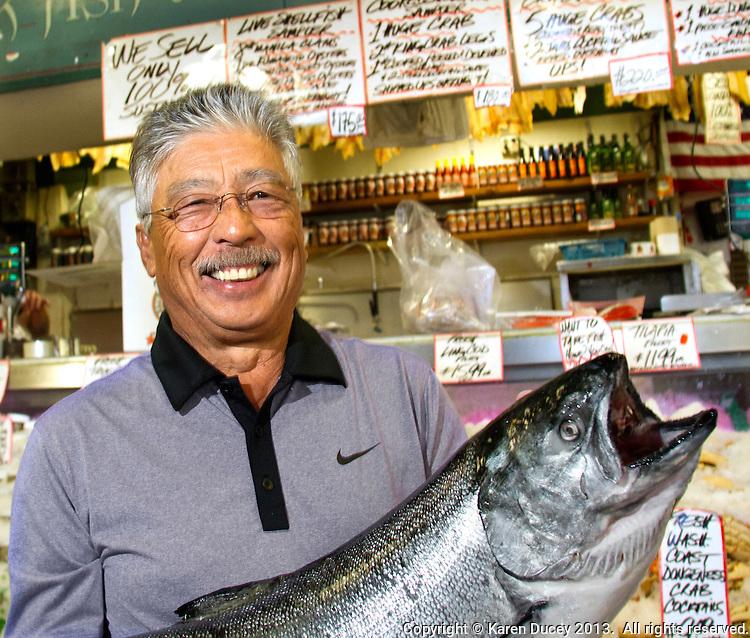 John Yokoyama, owner of Pike Place Fish market holds a wild-caught King salmon from Alaska in Seattle, Wash., on July 1, 2013. Yokoyama has owned the market since 1965. (photo © karenducey.com)