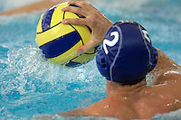 A waterpolo player palms the ball in the pool during competition.