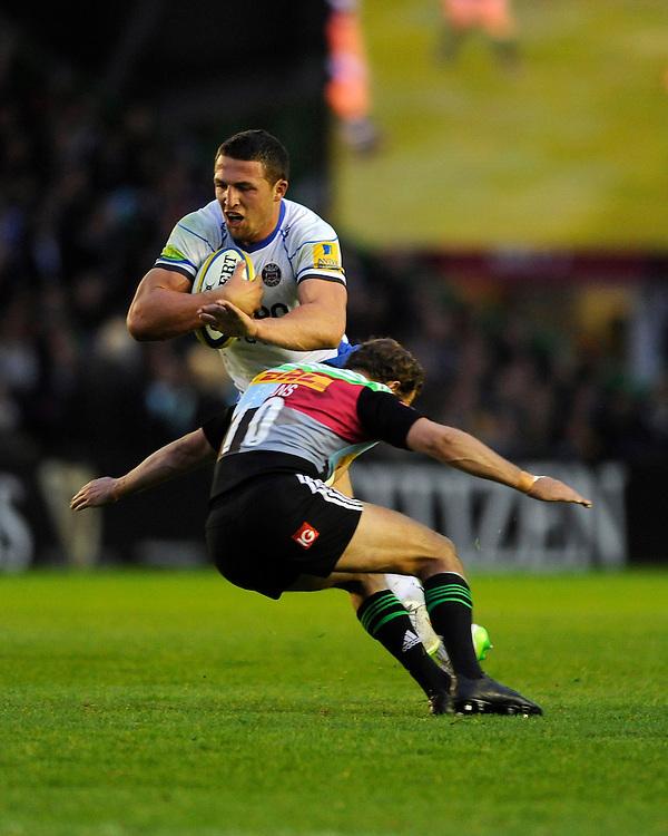 Sam Burgess of Bath Rugby is tackled by Nick Evans of Harlequins