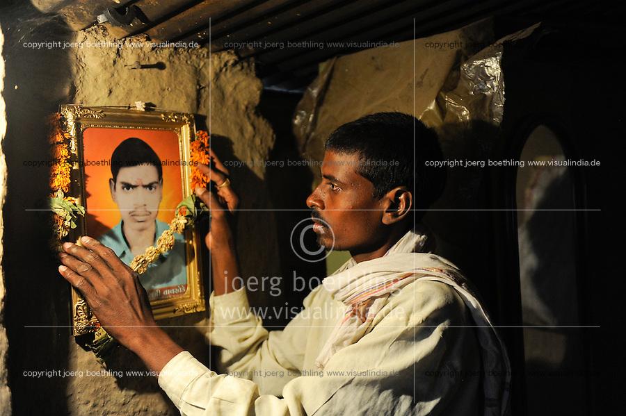 INDIA Maharashtra, farmer Prafull Ramdasji Wankhede with the picture of his died brother Prabhu Ramdasji Wankhede, who has committed suicide due to high debt and cotton crop failure in Vidarbha region / INDIEN Maharashtra, Region Vidarbha , Dorf Sonegaon, Baumwollfarmer Prafull Ramdasji Wankhede mit dem Foto seines verstorbenen Bruders Prabhu Ramdasji Wankhede, der nach Missernte und hoher Verschuldung Selbstmord begangen hat