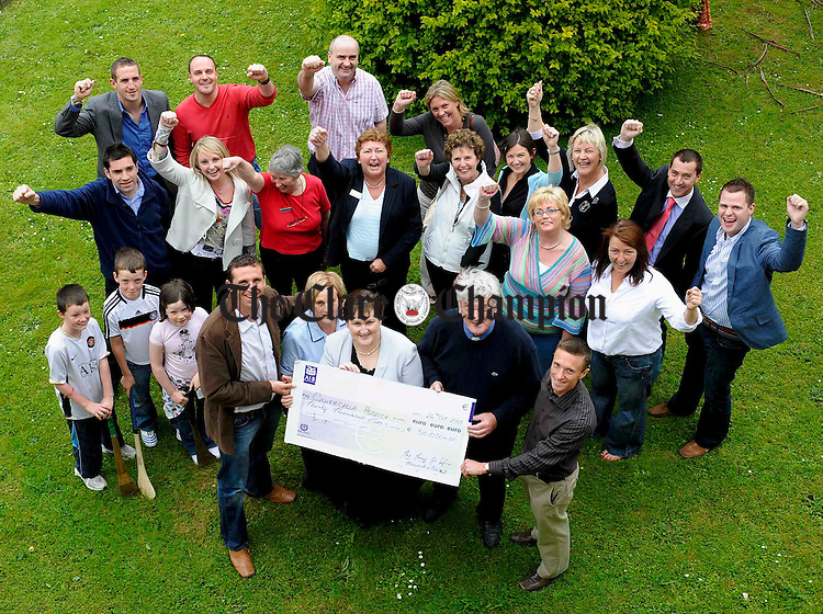 At the presentation of a cheque to the value of E30,000 raised locally by the Tony Griffin Foundation to Cahercalla Hospice were, at front, Tony Griffin, Helen Casey, nurse, Mary Maloney, fundraising co-ordinator, Fr Harry Bohan, chairman of the cahercalla board and Travis Mc Donagh, Foundation manager. Looking on are supporters, family, and fundraisers. Photograph by John Kelly.