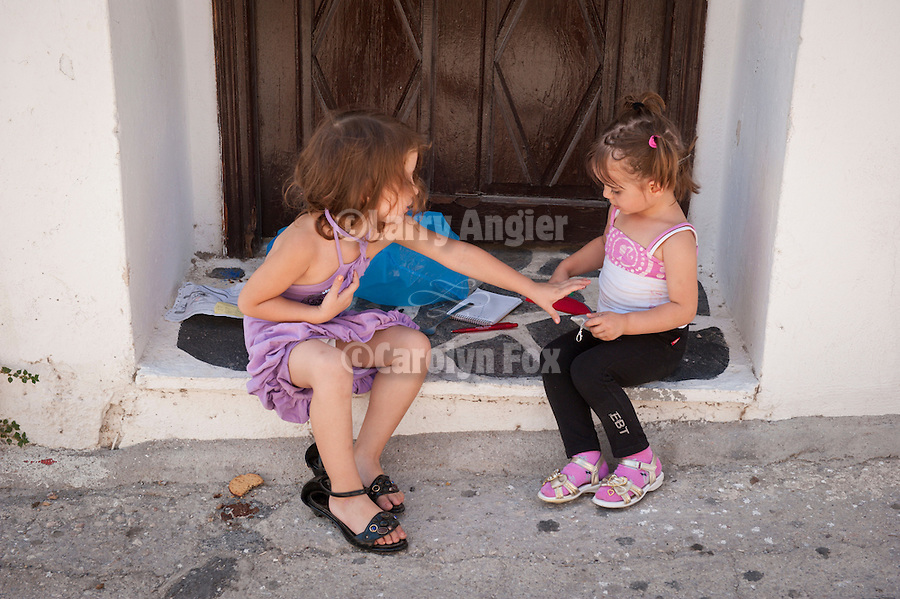 Two little girls sitting in a doorway and playing, Fira, Santorini, Greece.