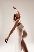 Pregnant woman standing with arms raised