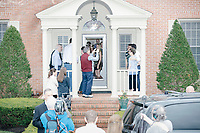 People greet Democratic presidential candidate and South Bend mayor Pete Buttigieg as he arrives to speak at a house party with the Bedford Democrats in Bedford, New Hampshire, on Sat., Apr. 20, 2019. The candidate stood on a chair throughout his speech.