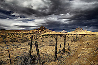 Cerro Guadalupe, Cabezon Peak, and Cerro Santa Clara in the Rio Puerco Valley in the San Juan Basin of northwestern New Mexico under a stormy sky at sunset.