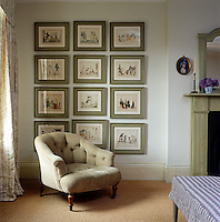 In this bedroom of a New York apartment the identical frames of the twelve French prints have all been painted grey/green to match the rest of the woodwork in the room