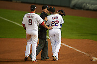Salt River Rafters first baseman Dominic Smith (22) is restrained by umpire Tom Woodring and third baseman Drew Ward (9) after base runner Aaron Brown (not pictured) ran into Smith while running through the bag during an Arizona Fall League game against the Glendale Desert Dogs on October 22, 2015 at Salt River Fields at Talking Stick in Scottsdale, Arizona.  Glendale defeated Salt River 7-5.  (Mike Janes/Four Seam Images)