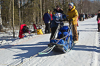 Elliot Anderson and team run past spectators on the bike/ski trail during the Anchorage ceremonial start during the 2014 Iditarod race.<br /> Photo by Britt Coon/IditarodPhotos.com