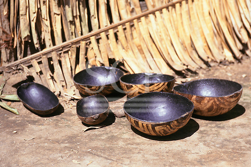 Koatinemo village, Brazil. Gourd vessels painted in traditional Assurini Indian designs next to a palm leaf.