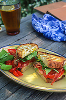 Rustic home grown tomato sandwich (BLT) with bacon and baby lettuce on picnic table
