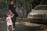 Romania. Iași County. Iasi. A grandmother and her granddaughter are walking in the street. The stylish child is dressed with a dress and wears a pink hat and sunglasses. She carries a doll in her right arm. A grey Mercedes car is parked under the streets and is covered with dust. A recycling bank is located on the street. As well as home recycling bins, there are many recycling banks across Iasi that can be used to recycle different materials and are located on streets across the town. Iași (also referred to as Iasi, Jassy or Iassy) is the largest city in eastern Romania and the seat of Iași County. Located in the Moldavia region, Iași has traditionally been one of the leading centres of Romanian social life. The city was the capital of the Principality of Moldavia from 1564 to 1859, then of the United Principalities from 1859 to 1862, and the capital of Romania from 1916 to 1918. 13.06.15 © 2015 Didier Ruef