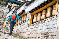 A woman at the Namche Bazar Buddhist temple looks at the prayer wheels, Nepal