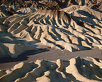 Sunrise light on eroded formations at Zabriskie Point; Death Valley National Park ,CA