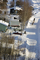 Aerial of Jamie Nelson mushing down street on the way out of Ruby during 2006 Iditarod Alaska Winter