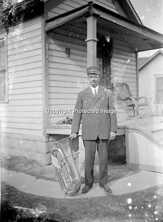 MUSICIAN BESIDE THE SHIPMAN HOUSE. The identity of the musician is uncertain, but his location is revealed by the address 851, which corresponds with the home of Edward and Clara Shipman at 851 University Avenue, located north of Vine Street between North Twelfth and Thirteenth Streets.<br /> <br /> The gentleman may be Edward Shipman (1863-1921), who worked as a porter and stockman at various Lincoln paint companies.  He is posing with his tuba with music attached. There were at least two African American bands in early Lincoln.<br /> <br /> <br /> Photographs taken on black and white glass negatives by African American photographer(s) John Johnson and Earl McWilliams from 1910 to 1925 in Lincoln, Nebraska. Douglas Keister has 280 5x7 glass negatives taken by these photographers. Larger scans available on request.