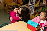 Preschool toddler-2s program girl watching as classmate says goodbye to her mother in the morning