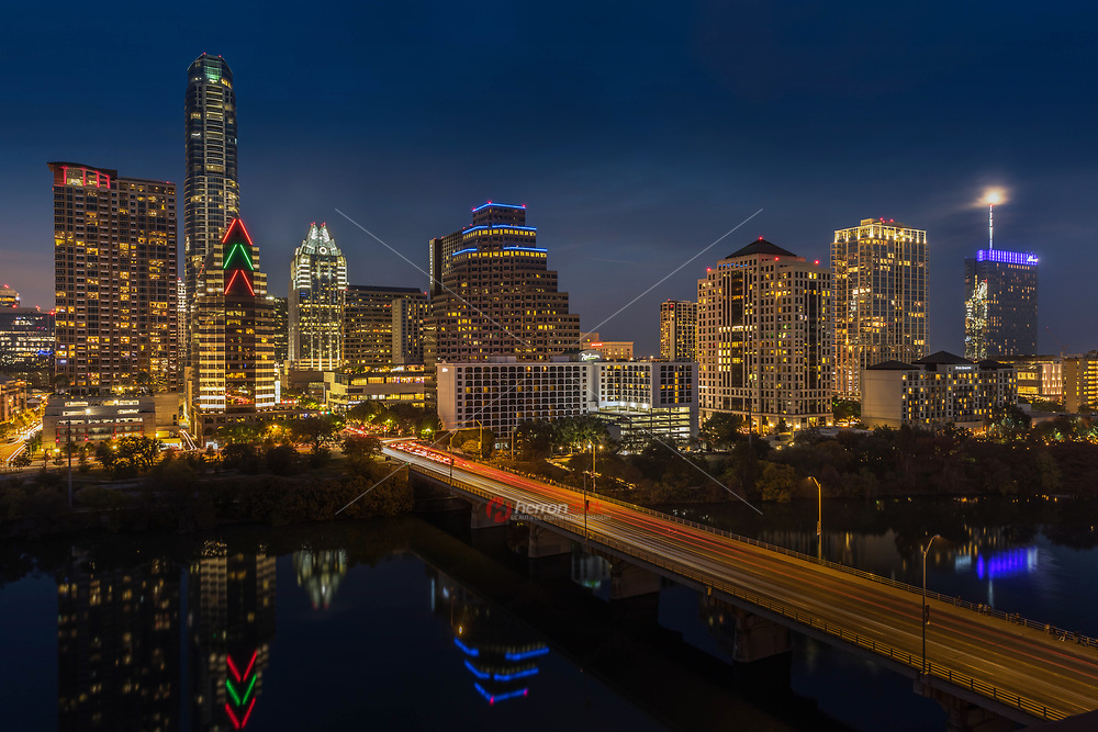 On a mild, December evening, the bright neon lights shine bright roll over the city in this Austin skyline image. This view of downtown Austin was captured from the Hyatt and looks out over Ladybird Lake. In the distance, the Austin icons - the Frost Bank Tower and the Austonian, rise into the blue sky with a new skyscraper joining the family, the Fairmont Hotel, illuminating the night sky.