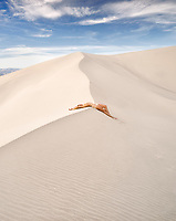 Woman laying on the edge of sand dunes. Death Valley National Park, CA