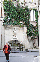 On a street in the old town A fountain with water and a bust of Nostradamus by Liotard de Lambesc in 1859. on the street corner of Rue Nostradamus, a woman walking, a tree vine clinging to the house facade, labyrinth. Fontaine Ancienne. Saint Remy Rémy de Provence, Bouches du Rhone, France, Europe