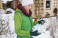 """Vogelbeobachtung im winterlichen Garten bei Schnee, Familie beim Vögel gucken, Kind füllt Zählhilfe aus, Protokoll, """"NABU Aktion Stunde der Wintervögel"""", family watching birds, bird watching in winter, garden, snow, binoculars"""