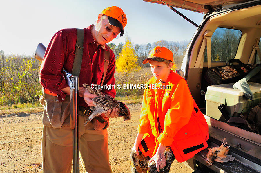 00515-074.11  Ruffed Grouse: Father and son admire bagged ruffed grouse. Note woodcock on tailgait of truck.