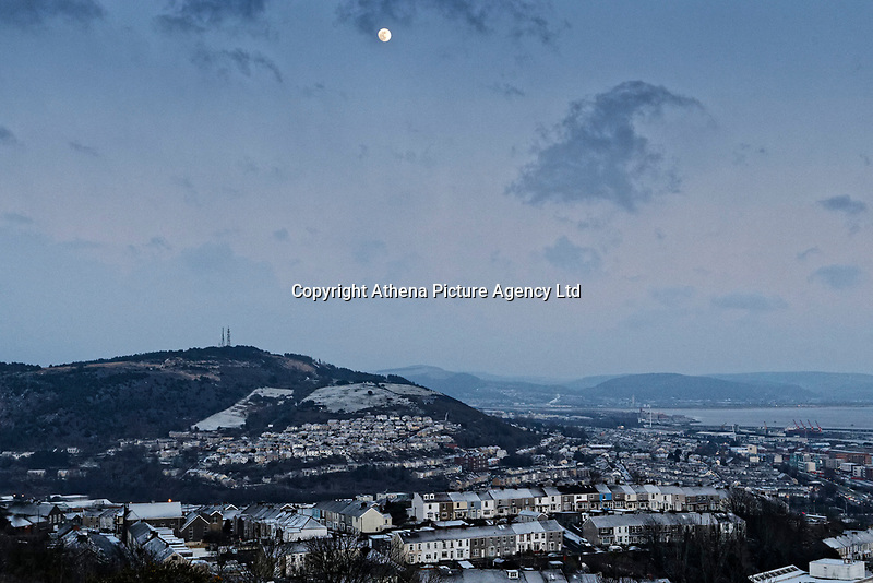 """Pictured: The lunar phonomenon known as Black Moon is seen over the St Thomas area of Swansea where snow caused by the """"Beast from the East"""" has covered it in Swansea, south Wales, UK. Wednesday 28 February 2018<br /> Re: Strong cold winds from the east have been affecting most parts of the UK with temperatures in some parts below zero."""