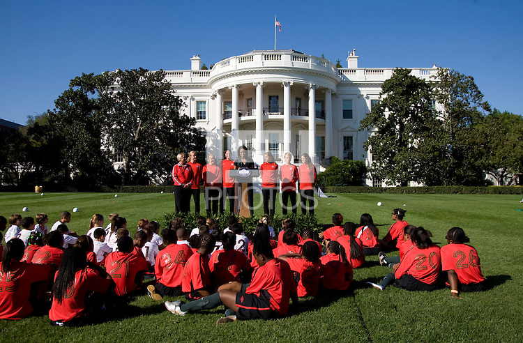 Michelle Obama talks to a group of young soccer players while flanked by members of the USWNT during a Lets Move! soccer clinic held on the South Lawn of the White House.  Let's Move! was started by Mrs. Obama as a way to promote a healthier lifestyle in children across the country.