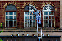 Painter  leans from ladder to apply white paint to old windows in Uptown Westerville,