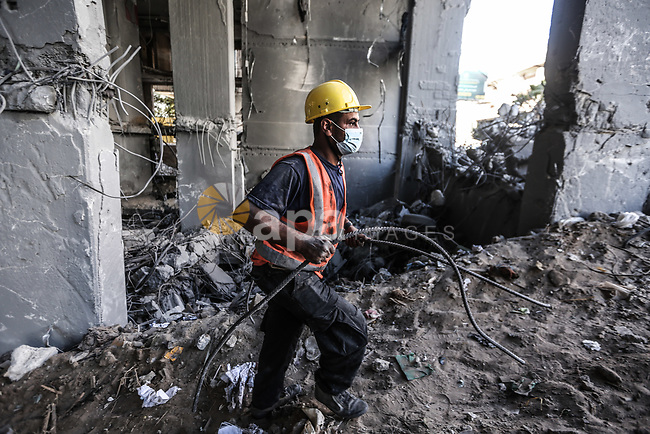 Palestinian workers remove the rubbles of al-Jawhara tower which was hit by Israeli airstrikes on May 12 during the recent Israeli military escalation, in Gaza city on June 15, 2021. The Egyptian-brokered truce ended 11 days of heavy Israeli bombing of Gaza and rocket fire from the impoverished coastal enclave into Israel. Israeli air strikes and artillery fire on Gaza killed 257 Palestinians, including 66 children, and wounded more than 1,900 people in 11 days of conflict from May 10, the health ministry in Gaza says.Photo by Bashar Taleb