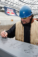 Steel worker Donald Geren signs the last piece of steel prior to it being placed during the topping off ceremony at Red Bull Arena in Harrison, NJ, on April 14, 2009.