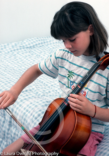 7 year old girl sitting on edge of bed playing musical instrument cello vertical closeup Caucasian