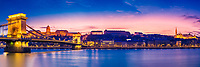 Colorful sunset panorama on the Danube River with lit-up Szechenyi Chain bridge, the Royal Palace, and Matthias Church, in Budapest Hungary