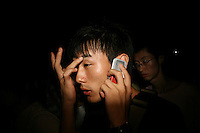 CHINA. Beijing. A man using his cellphone whilst watching the opening ceremony of the Beijing Summer Olympics. 2008