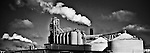 Industrial image of tanks with steam and clouds in black and whtie