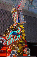 Las Vegas, Nevada.  Fremont Street.  Glitter Gulch Cowgirl Sign, with Zoomline Zip Line Rider Going Past.