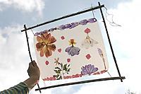 Kinder basteln ein Fensterbild mit Blüten, Mädchen hält fertiges Fensterbild mit durchscheinenden Blüten gegen den Himmel