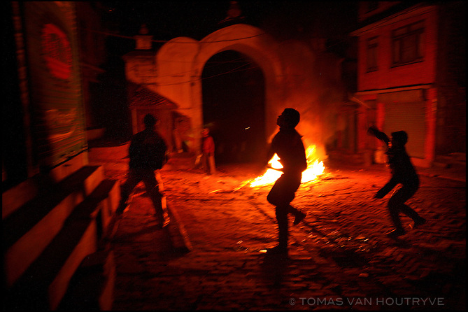 Rioters throw stones at police from behind a fire that they started in Bhaktapur, Nepal on 15 December 2005. The day after a Royal Nepal Army soldier went on a rampage and killed 11 civilians in a Hindu temple, angry residents closed down Bhaktapur's streets with violent riots and surrounded the hospital holding the victim's bodies demanding justice. Since the Royal Nepal Army entered into conflict against Nepal's Maoist rebels, it has come under heavy criticism for alledged human rights abuses and lack of accountablity.<br />
