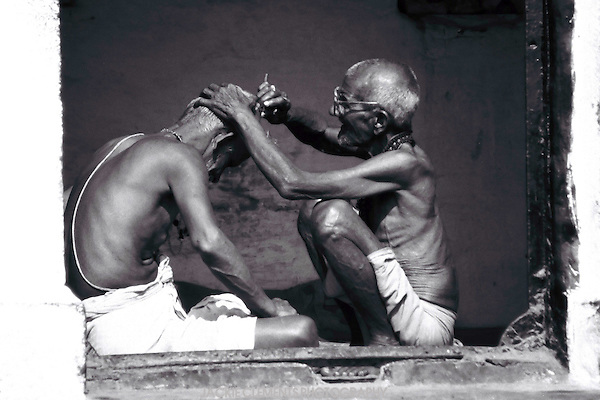 A man has his head shaved in preparation  for a prayer ritual, or puja, by the sacred Ganges River at Varanasi.