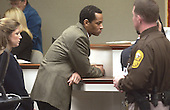Sniper suspect John Allen Muhammad,center, is watched by a sheriff's deputy as he listens to a bench conference along with defense attorney, Christie Leary, during his trial in courtroom 10 at the Virginia Beach Circuit Court in Virginia Beach, Virginia on November 5, 2003. <br /> Credit: Dave Ellis - Pool via CNP